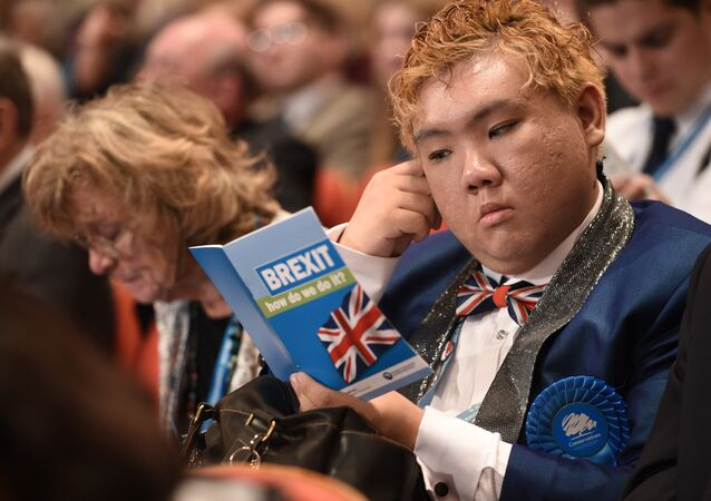 A delegate reads a leaflet entitled BREXIT, how do we do it? as he sits in the audience on the second day of the annual Conservative Party conference at the International Convention Centre in Birmingham, central England, on October 3, 2016.