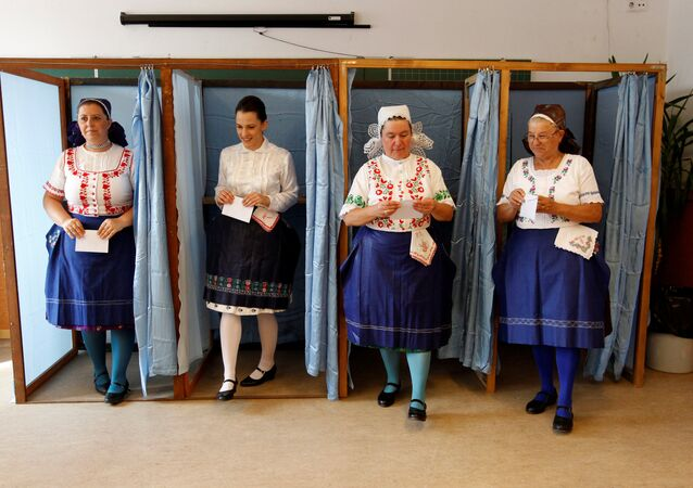 Hungarian women wearing traditional costume leave a voting booth at a polling station during a referendum on EU migrant quotas in Veresegyhaz, Hungary, October 2, 2016.