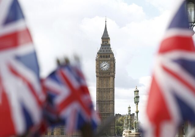 Union flags on sale at a souvenir stall fly in the breeze opposite the Houses of Parliament in London, Britain