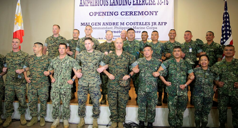 US Marine Corps and Philippine Marine Corps personnel link arms during the opening ceremony of annual Philippines-US amphibious landing exercise (PHILBLEX) inside the marines headquarters in Taguig city, metro Manila, Philippines October 4, 2016.