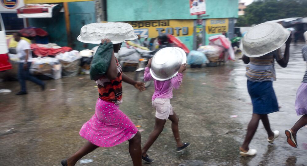 Women cover their heads with pans as they walk in a light rain brought by Hurricane Matthew in Port-au-Prince, Haiti, Tuesday, Oct. 4, 2016.