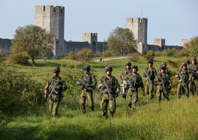 A squad from Skaraborg Armoured Regiment, currently training on the island of Gotland in the Baltic, patrols outside Visby's 13th century city wall, Sweden