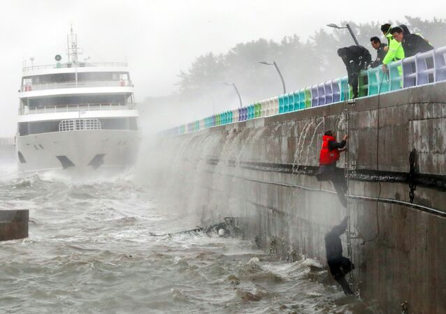 South Korean coast guards try to rescue crew members of a stranded passenger ship in the aftermath of typhoon Chaba in the southern city of Yeosu