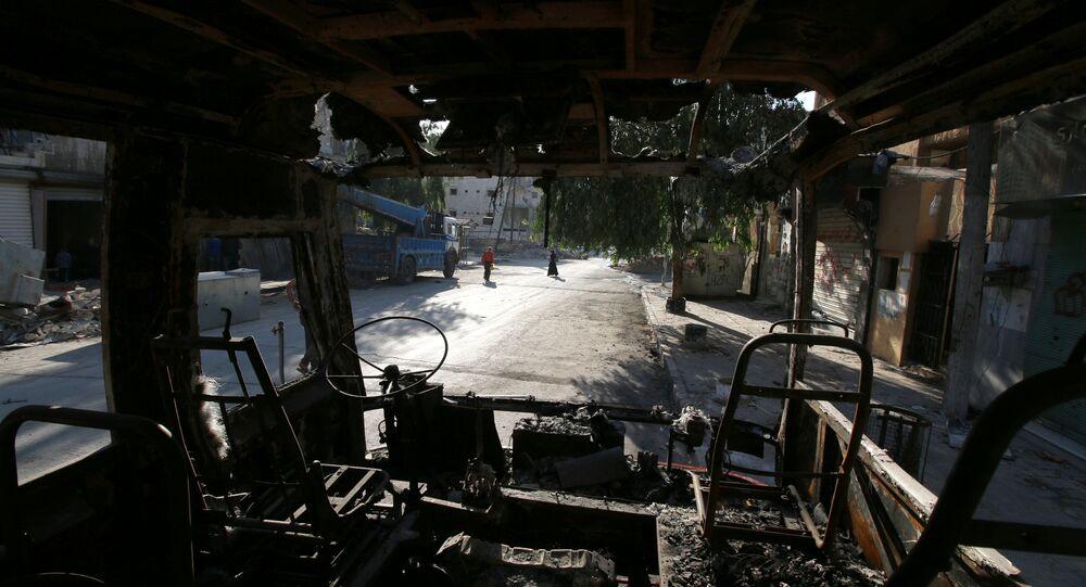 People walk past a burnt bus in the rebel held Seif al-Dawla neighbourhood of Aleppo, Syria October 6, 2016