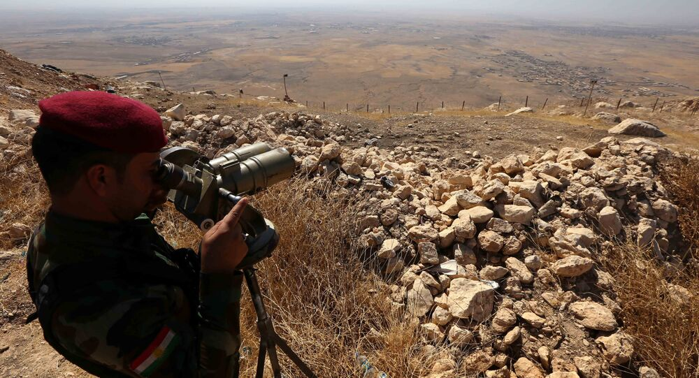 An Iraqi Kurdish Peshmerga fighter looks through binoculars on the top of Mount Zardak, about 25 kilometres east of Mosul, on October 6, 2016