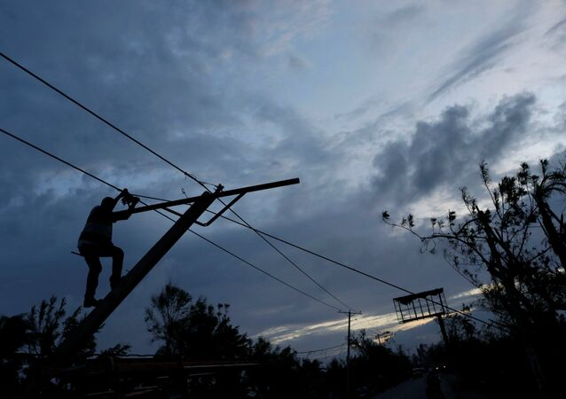 A worker for an electricity company fixes a power line affected by Hurricane Matthew on the outskirts of Les Cayes, Haiti, October 6, 2016