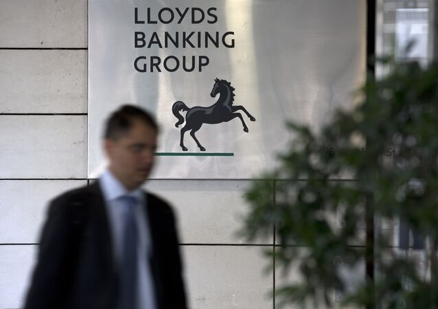 A man passes the entrance to the headquarters of Lloyds Banking Group in the City of London on July 28, 2016