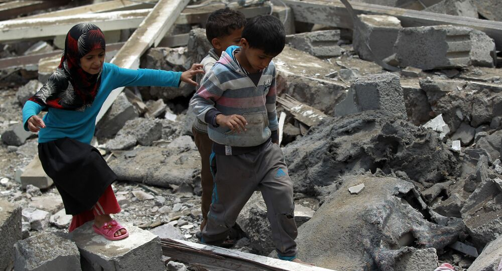 Yemeni children walk amidst the rubble of a house in Yemen's Huthi rebel-held capital Sanaa on August 11, 2016.