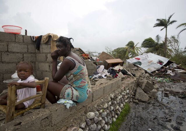 Victor Farah and her daughter sit in the ruins of their home destroyed by Hurricane Matthew in Les Cayes, Haiti, Thursday, Oct. 6, 2016. Two days after the storm rampaged across the country's remote southwestern peninsula, authorities and aid workers still lack a clear picture of what they fear is the country's biggest disaster in years.