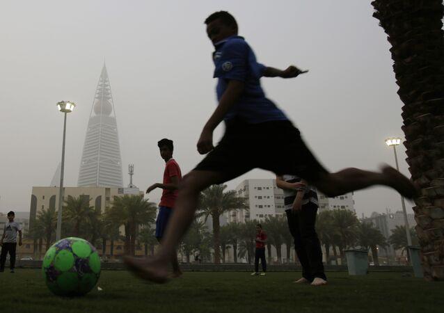 April 25, 2015. Saudi youths play soccer in a park during a dust storm in Riyadh, Saudi Arabia.