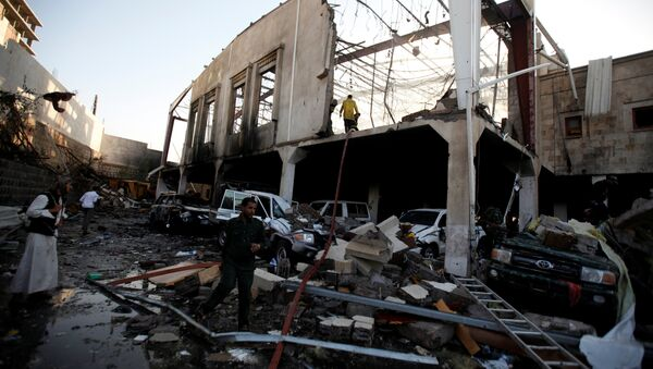 People stand at the site of an airstrike which witnesses said was by Saudi-led coalition aircraft on mourners at a hall where a wake for the father of Jalal al-Roweishan, the interior minister in the Houthi-dominated Yemeni government, was being held, in Sanaa, Yemen October 8, 2016 - Sputnik International