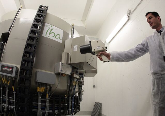 A technicians participates in the manufacturing of 'radioelements' during the unveiling of the cyclotron, a production unit of isotopes used in medical diagnosis to locate cancerous cells, on November 24, 2009 in the Saint-Louis hospital in Paris