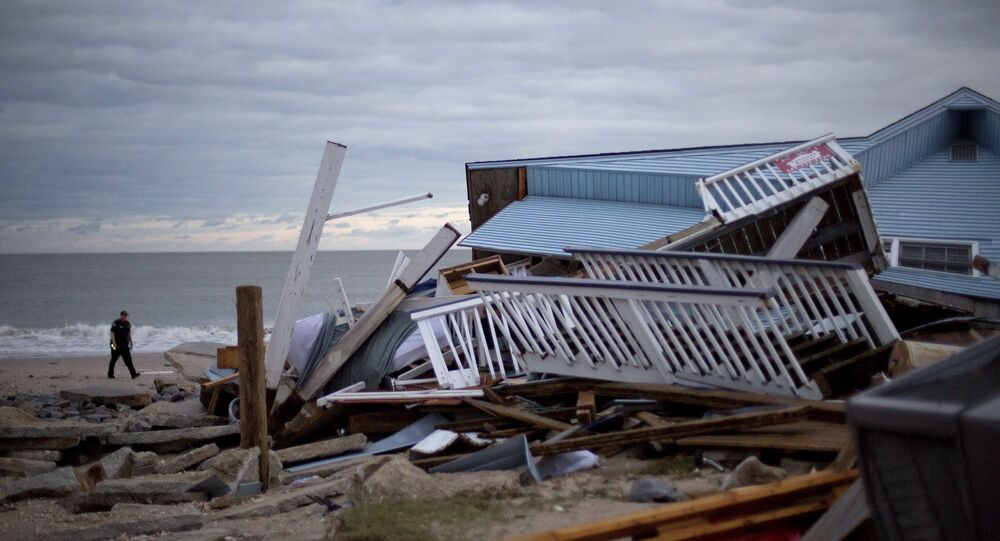 A police officer walks past the remnants of a home leveled by Hurricane Matthew after it hit the tiny beach community of Edisto Beach, S.C., Saturday, Oct. 8, 2016.