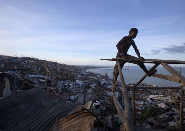 A resident works to repair his roof after it was ripped away by Hurricane Matthew in Jeremie, Haiti, Friday, Oct. 7, 2016