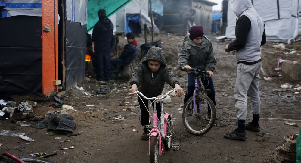 Afghan children ride their bicycles in a makeshift migrants camp near Calais, France, Thursday Feb. 25, 2016