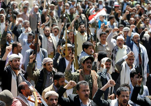 Armed people demonstrate outside the United Nations offices against Saudi-led air strikes on funeral hall in Sanaa, the capital of Yemen, October 9, 2016