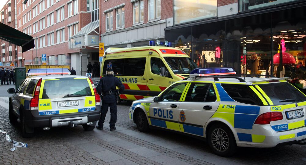 Policemen and ambulance workers stand in front of the entrance of a building in Storgatan in central Malmo (File)