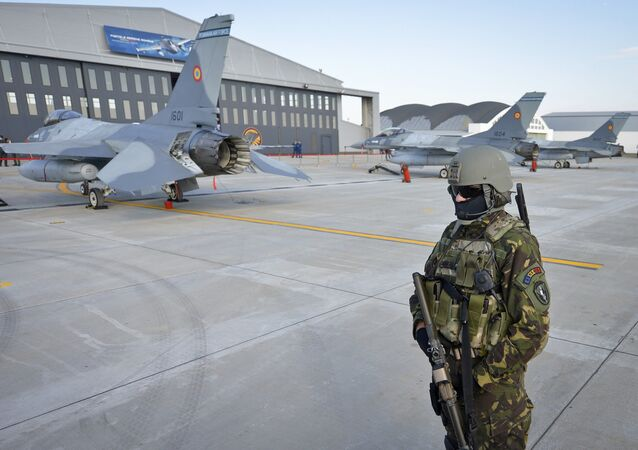 A Romanian soldier secures the perimeter around Romanian Air Force F16 fighter jets parked on the runway of the Air Base 86, in Borcea, southern Romania, Friday, Oct. 7, 2016