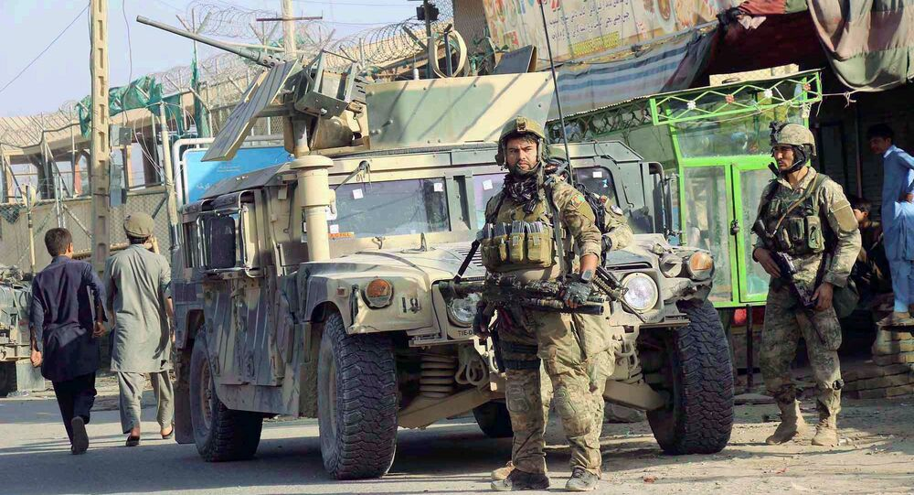 Afghan security forces keep watch in front of their armoured vehicle in Kunduz city, Afghanistan October 4, 2016