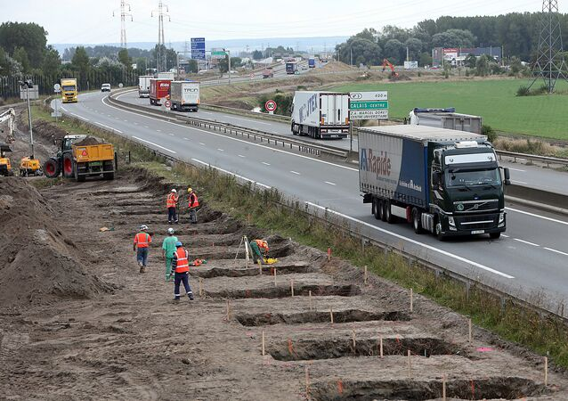 Workers begin construction of a 4-meter-high wall along the highway leading to the Calais port, outside Calais, northern France, Tuesday, Sept. 20, 2016