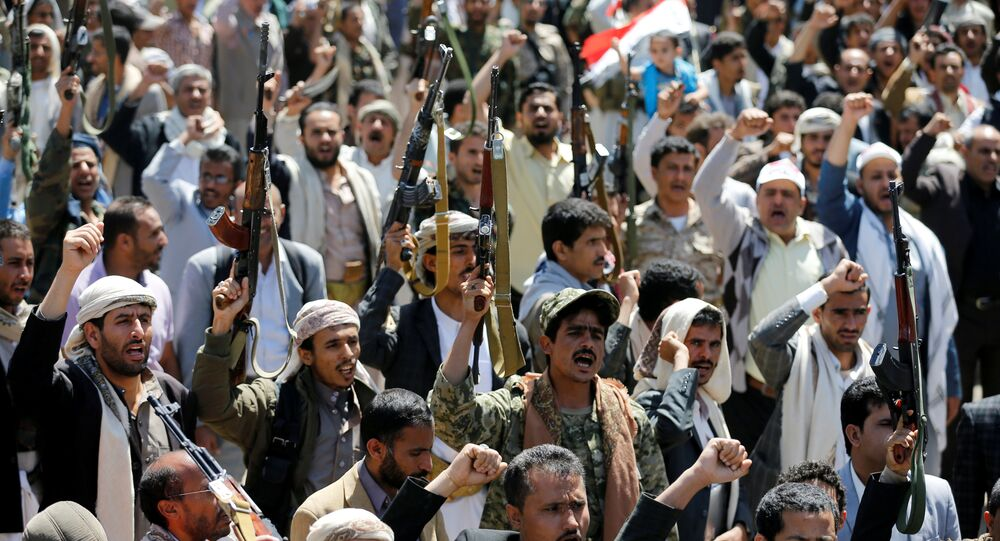 Armed people demonstrate outside the United Nations offices against Saudi-led air strikes on funeral hall in Sanaa, the capital of Yemen, October 9, 2016.