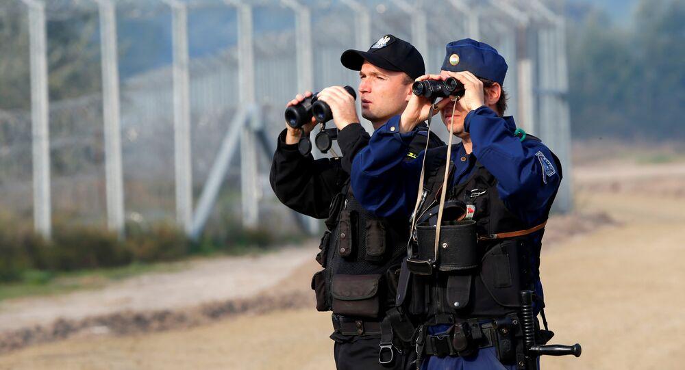 Hungarian and Polish policeman patrol at the Hungary and Serbia border fence near the village of Asotthalom, Hungary, October 2, 2016 as Hungarians vote in a referendum on the European Union's migrant quotas.