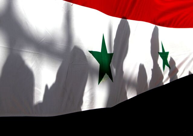 The shadows of people on a Syrian national flag are seen while they attend a peace march to mark International Day of Peace in Damascus.