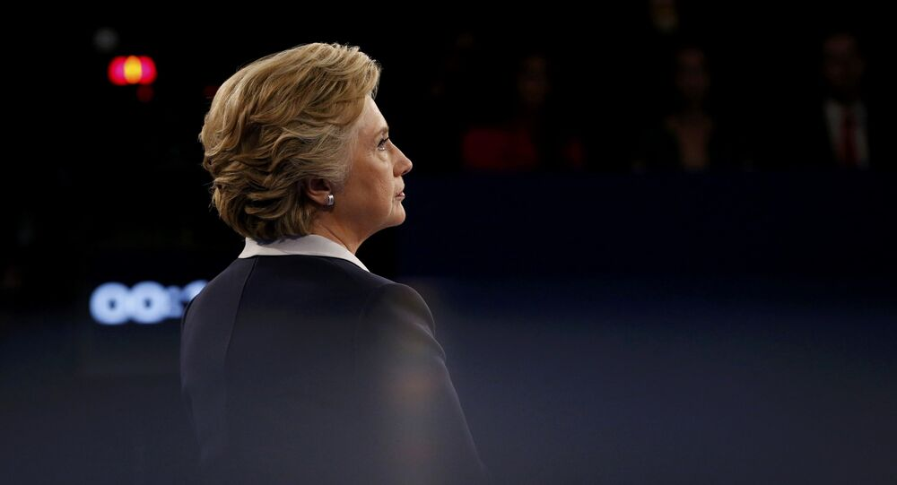 Democratic U.S. presidential nominee Hillary Clinton listens as Republican U.S. presidential nominee Donald Trump (not pictured) speaks during their presidential town hall debate at Washington University in St. Louis, Missouri, U.S., October 9, 2016.