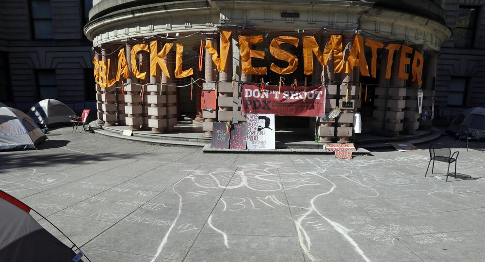 A raised raised is crawled in chalk as large letters saying Black Lives Matter hang on the portico at City Hall after the building was shut down due to a protest in Portland, Ore., Wednesday, Oct. 12, 2016.