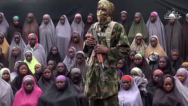 This file photo taken on August 14, 2016 shows a video grab image created on August 14, 2016 and taken from a video released on youtube purportedly by Islamist group Boko Haram showing what is claimed to be one of the groups fighters at an undisclosed location standing in front of girls allegedly kidnapped from Chibok in April 2014. - Sputnik International