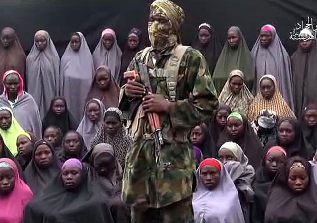 This file photo taken on August 14, 2016 shows a video grab image created on August 14, 2016 and taken from a video released on youtube purportedly by Islamist group Boko Haram showing what is claimed to be one of the groups fighters at an undisclosed location standing in front of girls allegedly kidnapped from Chibok in April 2014.