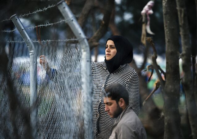 A couple stands behind a fence as refugees and migrants wait to cross the Greek-Macedonian border near the town of Gevgelija on March 3, 2016.