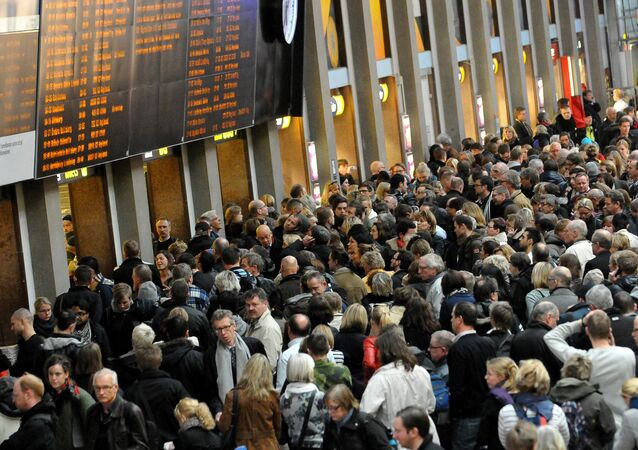Train passengers gather in front of the info panel at Central Station Stockholm