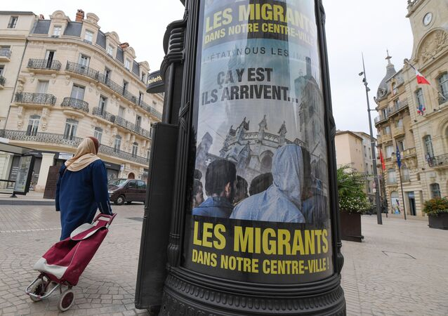 A woman walks by a poster reading They are coming, Migrants in our town centre in a street of Beziers, southern France, on October 12, 2016.