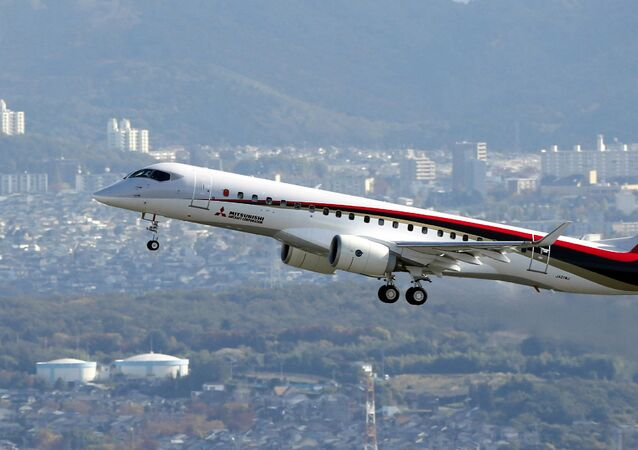 Japan's first domestically produced passenger jet, the Mitsubishi Regional Jet (MRJ), flying over the city of Komaki in the Aichi prefecture, central Japan on November 11, 2015 for its maiden test flight.