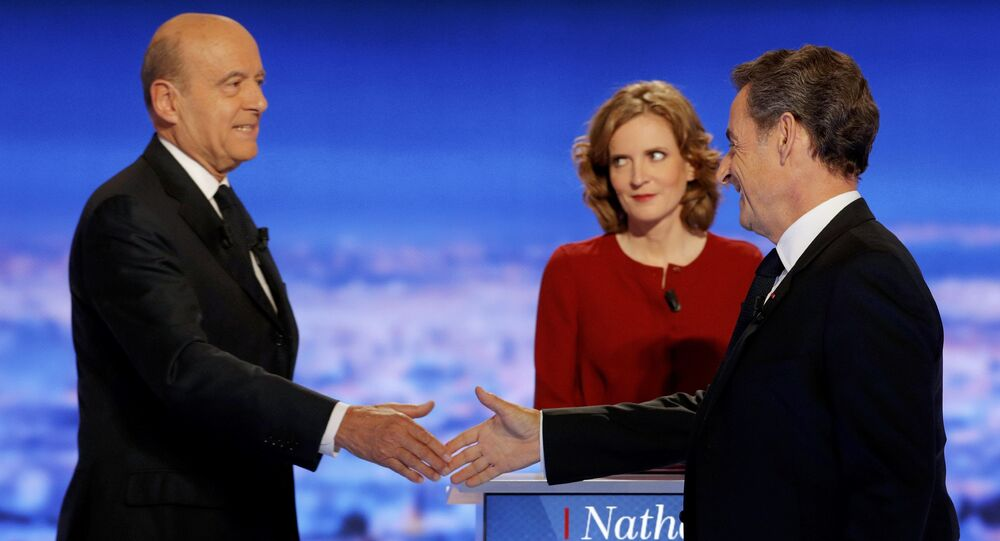 French politicians Alain Juppe (L) and Nicolas Sarkozy (R) shake hands as Nathalie Kosciusko-Morizet looks on before the first prime-time televised debate for the French conservative presidential primary in La Plaine Saint-Denis, near Paris, France, October 13, 2016.