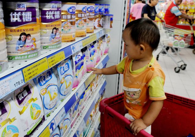 A Chinese baby plays beside tins of milk powder made by NASDAQ-listed Synutra (L-1) on sale at a supermarket in Beijing on August 9, 2010
