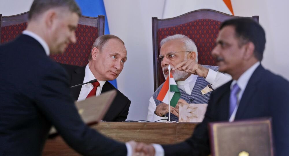 Indian Prime Minister Narendra Modi, rear right, talks with Russian President Vladimir Putin as officials of two countries exchange agreements after bilateral meeting in the beach resort state of Goa in western India, Saturday, Oct. 15, 2016