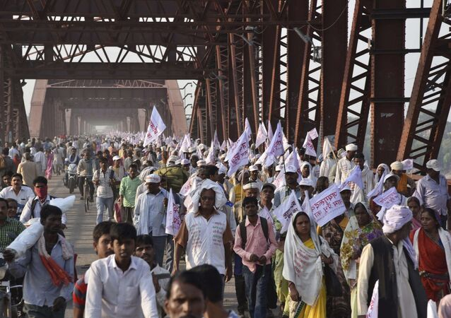 Hindu pilgrims hold religious flags and walk on a crowded bridge after a stampede on the same bridge on the outskirts of Varanasi, India, Saturday, Oct. 15, 2016