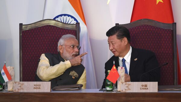 India Prime Minister Narendra Modi (L) gestures while talking with China's President Xi Jingping during the BRICS leaders' meeting with the BRICS Business Council at the Taj Exotica hotel in Goa on October 16, 2016 - Sputnik International
