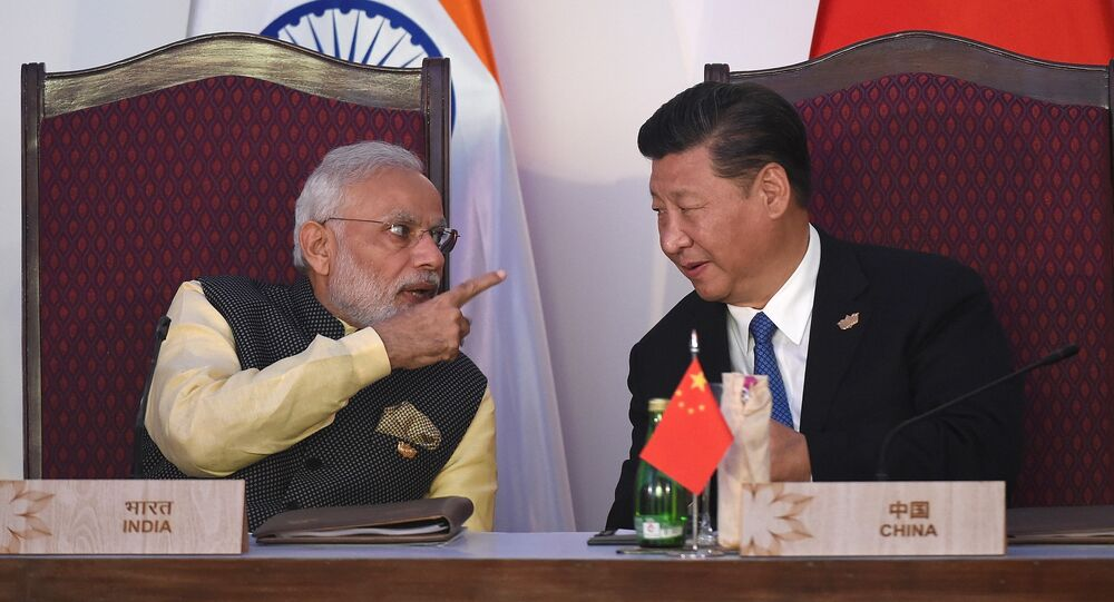 India Prime Minister Narendra Modi (L) gestures while talking with China's President Xi Jingping during the BRICS leaders' meeting with the BRICS Business Council at the Taj Exotica hotel in Goa on October 16, 2016