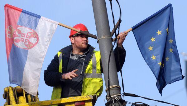 A worker arranges flags of Serbia and EU on a lamppost in Belgrade (File) - Sputnik International