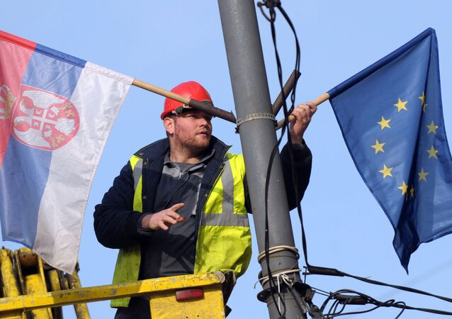 A worker arranges flags of Serbia and EU on a lamppost in Belgrade (File)