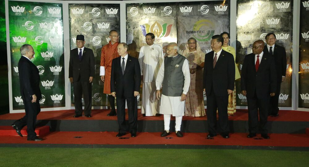 Brazilian President Michel Temer, left, walks to join leaders of BRICS countries, from left bottom row, Russian President Vladimir Putin, Indian Prime Minister Narendra Modi, Chinese President Xi Jinping, and South African President Jacob Zuma and BIMSTEC leaders, second row from left, Nepalese Prime Minister Pushpa Kamal Dahal, Bhutanese Prime Minister Tshering Tobgay, Sri Lankan President Maithripala Sirisena, Bangladesh Prime Minister Sheikh Hasina, Myanmar's Foreign Minister Aung San Suu Kyi and Thailand's Vice Minister for Foreign Affairs Virasakdi Futrakul, for a group photo at the BRICS and BIMSTEC, or Bay of Bengal Initiative for Multi-Sectoral Technical and Economic Cooperation, summit in Goa, India, Sunday, Oct. 16, 2016