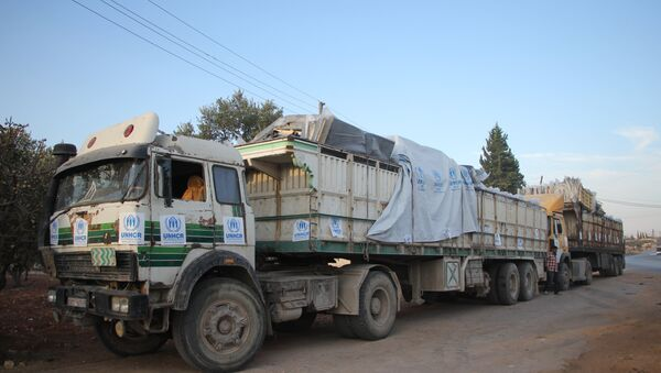 Trucks carrying aid are seen on the side of the road in the town of Orum al-Kubra on the western outskirts of the northern Syrian city of Aleppo on September 20, 2016 - Sputnik International