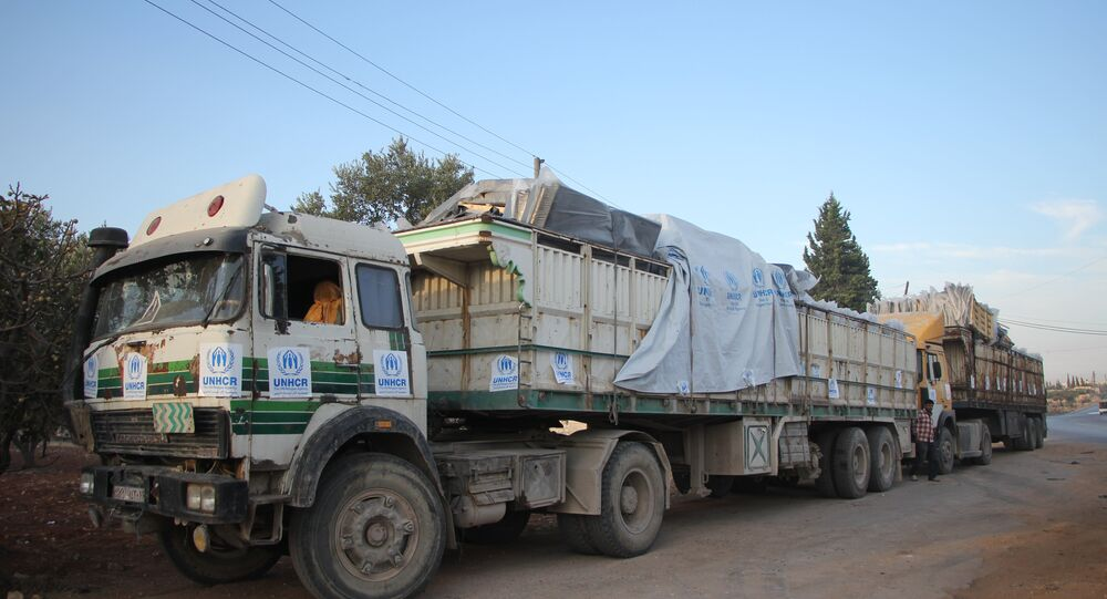 Trucks carrying aid are seen on the side of the road in the town of Orum al-Kubra on the western outskirts of the northern Syrian city of Aleppo on September 20, 2016