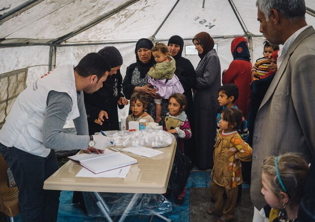 Civilians displaced by heavy fighting between Iraqi security forces and ISIS militants wait to be seen by a doctor in a tent set up by MSF, or Doctors Without Borders, to provide medical aid at a shelter in Makhmour, near Mosul, Iraq, March 28, 2016