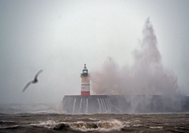 Waves crash over Newhaven Lighthouse on the south coast of England