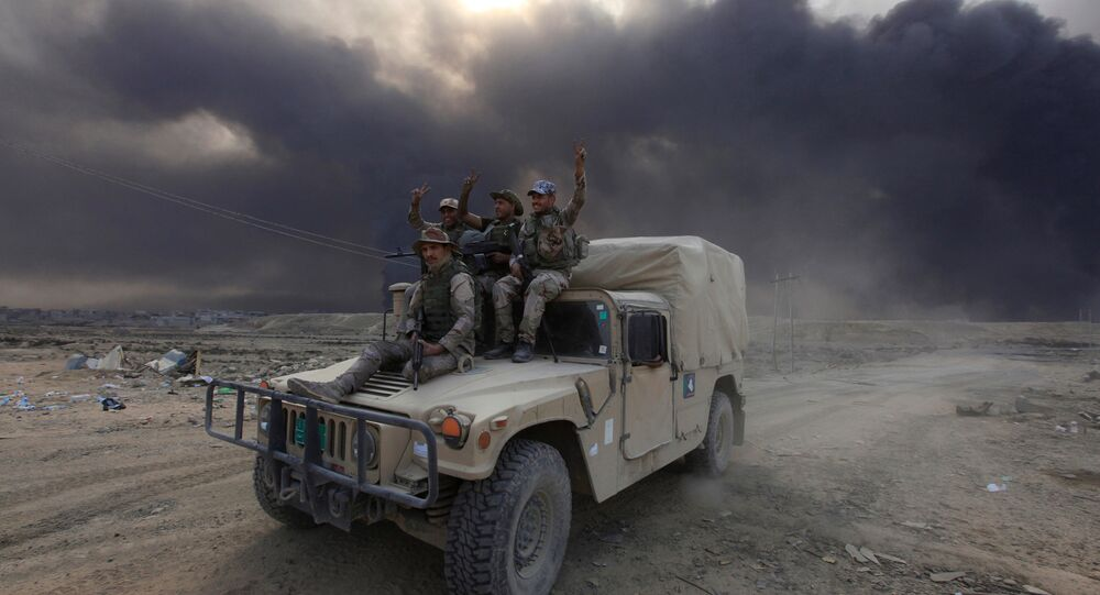 Iraqi army personnel ride on a military vehicle in Qayyarah, during an operation to attack Islamic State militants in Mosul, Iraq