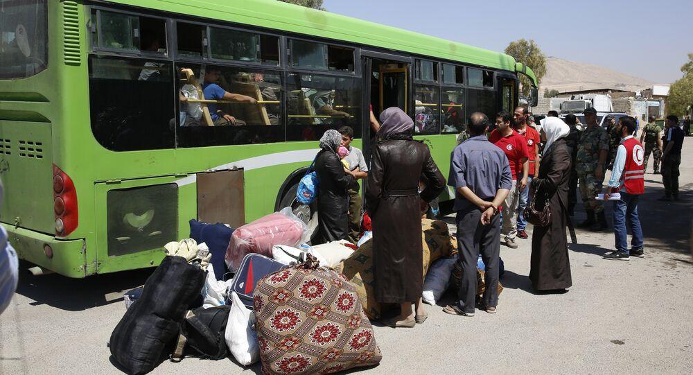 People board buses leaving the Moadamiyeh suburb of Damascus, Syria